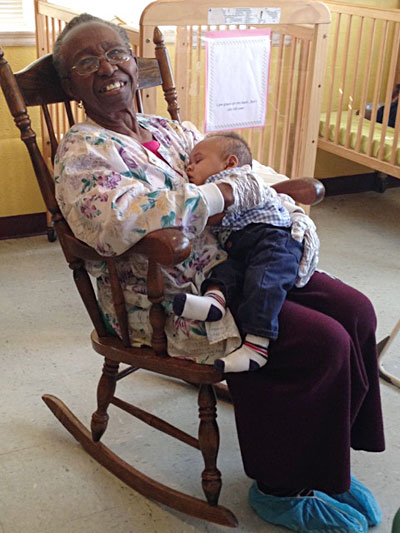 Caregiver in rocking chair with infant